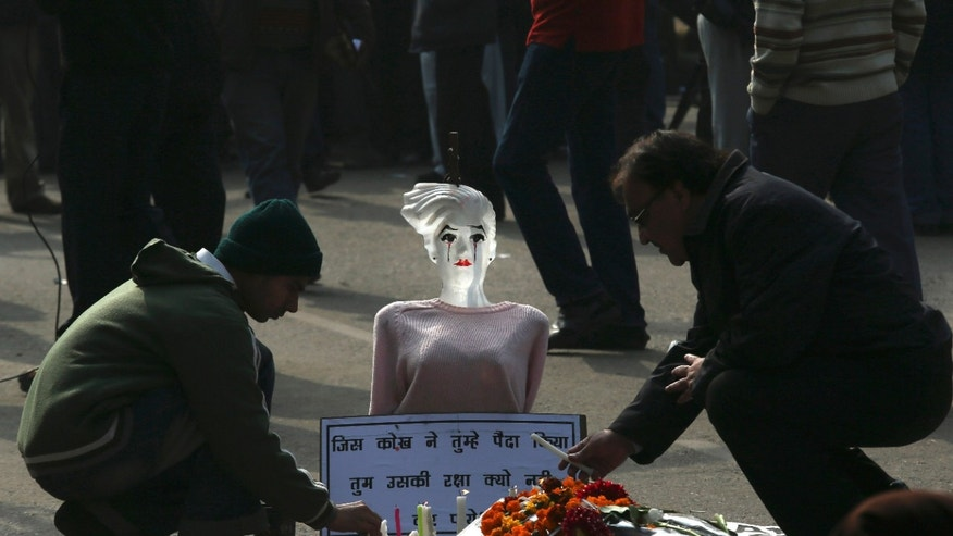 "Indian men place candles in front of a mannequin during a protest in New Delhi, India, Monday, Dec. 31, 2012. A young woman who died after being gang-raped and beaten on a bus in India's capital was cremated privately as millions of grieving, angry residents demanded greater protection for women from sexual violence. The placard reads as, ""Protect women who give birth.""  (AP Photo/Manish Swarup)"