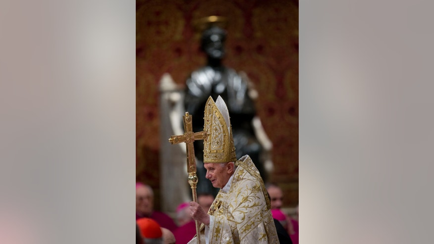 Pope Benedict XVI passes in front of a statue of St. Peter as he arrives in St. Peter's Basilica to celebrate a New Year's Eve vespers service at the Vatican, Monday, Dec. 31, 2012. (AP Photo/Andrew Medichini)