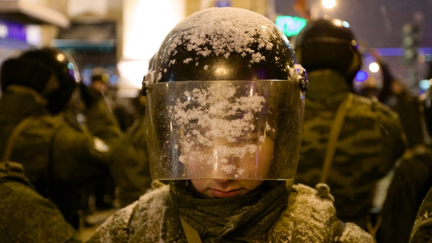 Dec. 31, 2012: A Russian Interior Ministry soldier peers through his snow-covered helmet as he and others block Triumphalnaya square during an unsanctioned rally in downtown Moscow, Russia.
