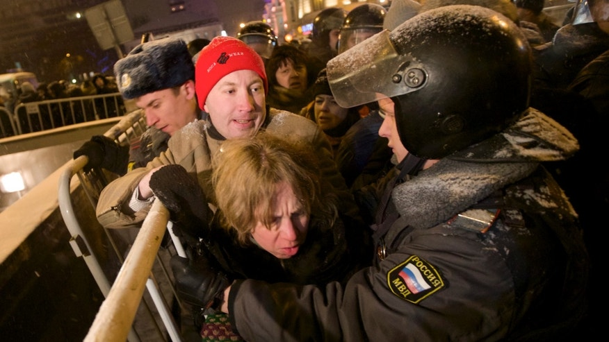 Dec. 31, 2012: Russian police officers push protesters off Triumphalnaya square during an unsanctioned rally in downtown Moscow, Russia.