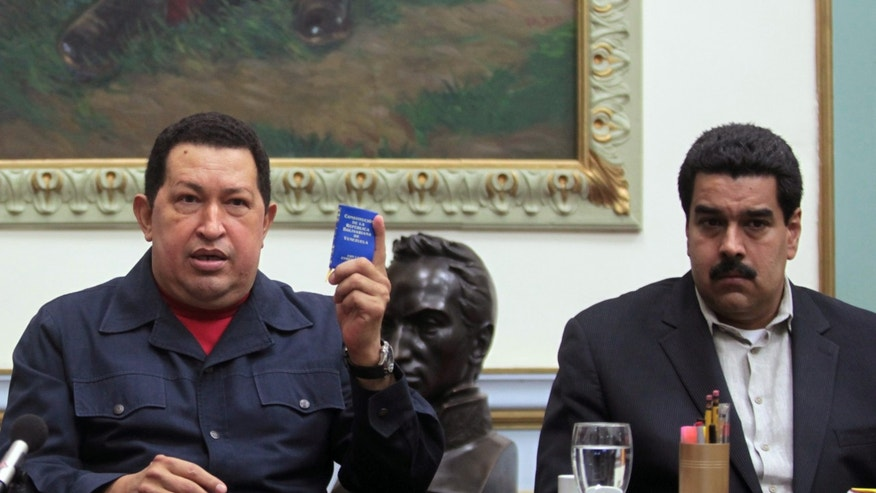 Dec. 8, 2012: Venezuela's President Hugo Chavez holds up a copy of the Venezuelan national constitution as his Vice President Nicolas Maduro looks on during a televised speech in Caracas.