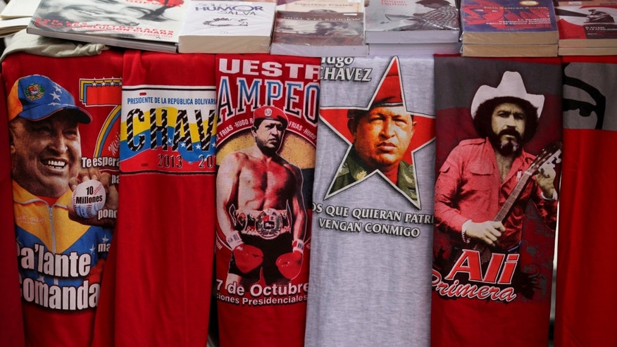 Iconic T-shirts styled with images of Venezuela's President Hugo Chavez are displayed for sale next to a T-shirt of Venezuelan musician Ali Primera, in Caracas, Venezuela, Friday, Dec. 28, 2012. The obsessive, circular conversations about Chavez's health dominate family dinners, plaza chit-chats and social media sites in this country on edge since its larger-than-life leader went to Cuba for emergency cancer surgery more than two weeks ago. The man whose booming voice once dominated the airwaves for hours at a time has not been seen or heard from since.(AP Photo/Fernando Llano)