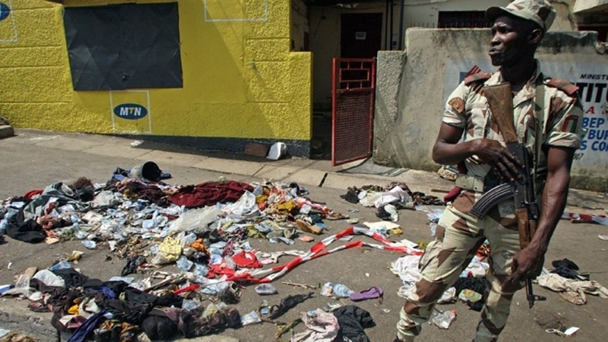 Jan, 1, 2013: An Ivory Coast troop stands next to the belongings of people involved in a deadly stampede in Abidjan, Ivory Coast. The death toll is expected to rise, according to rescue workers. (AP)