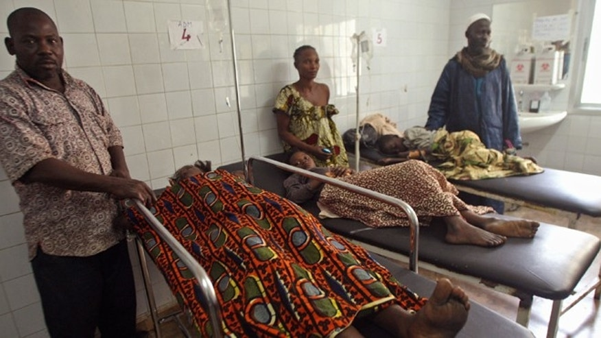 Jan. 1, 2013: Injured people are seen at a hospital with their family members standing with them, after they were involved in a  stampeded in Abidjan, Ivory Coast. (AP)
