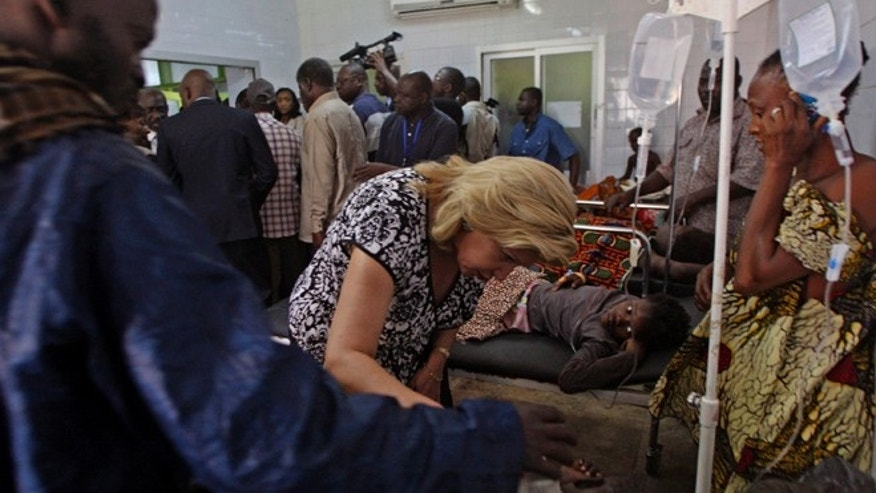 Jan. 1, 2013: Ivory Coast First Lady Dominique Ouattara, center left, speaks with a person injured in a stampede as they are treated at a hospital in Abidjan, Ivory Coast. (AP)