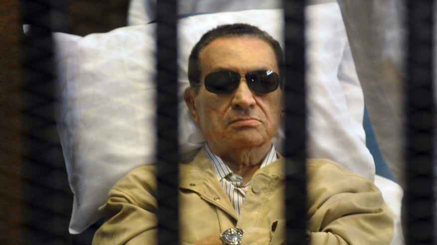 June 2, 2012: In this file photo, Egypt's ex-President Hosni Mubarak lays on a gurney inside a barred cage in the police academy courthouse in Cairo, Egypt.