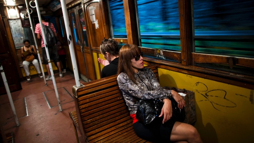 Passengers travel in a wooden carriage car on the historic subway system, Line A, in Buenos Aires, Argentina, Wednesday, Jan. 2, 2013. The city government announced that the almost 100-year-old 'La Brugeoise' wooden carriages will be replaced in a short time by modern Chinese units. (AP Photo/Natacha Pisarenko)