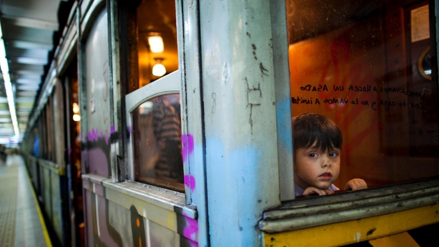 "A child looks through the window of a wooden carriage car on the historic subway system, Line A, in Buenos Aires, Argentina, Wednesday, Jan. 2, 2013. The city government announced that the almost 100-year-old 'La Brugeoise""wooden carriages will be replaced in a short time by modern Chinese units. (AP Photo/Natacha Pisarenko)"