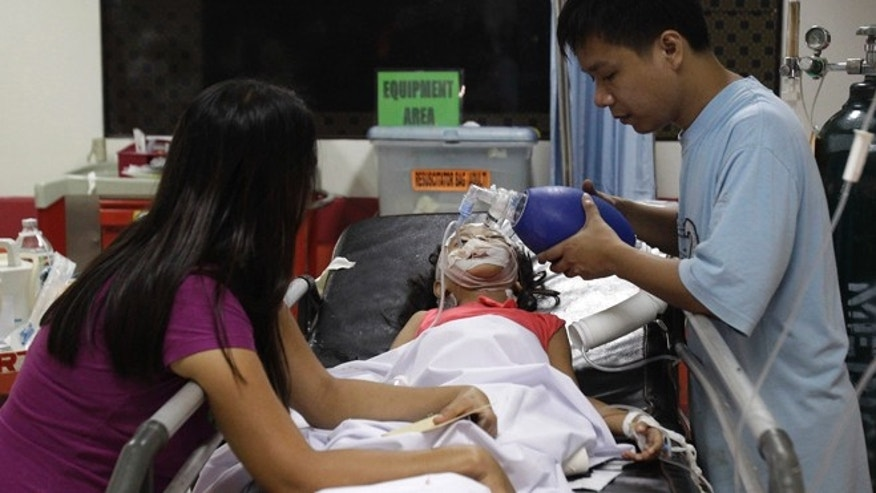 Jan. 1, 2013: Seven-year-old Stephanie Nicole Ella lays in a bed as her parents aid in giving her life support while being treated at the East Avenue Medical Center  after she was hit in the head by a stray bullet while watching fireworks with her family during New Year's Eve revelry, in suburban Quezon city, north of Manila, Philippines. Ella died in a hospital Wednesday heightening calls to halt one of Asia's most violent celebrations of the new year.