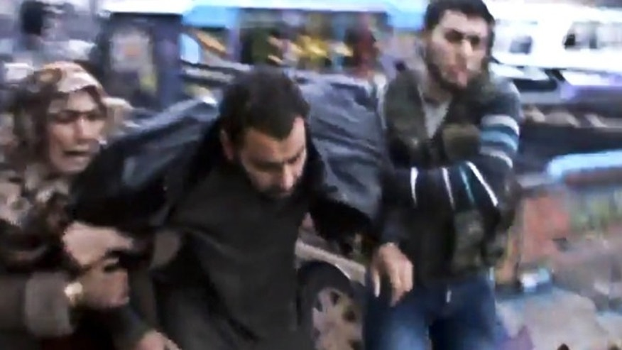 Dec. 23, 2012: This image taken from video obtained from the Shaam News Network, which has been authenticated based on its contents and other AP reporting, shows Syrians helping a wounded man after a government airstrike hit the Hama Suburb of Halfaya, Syria.