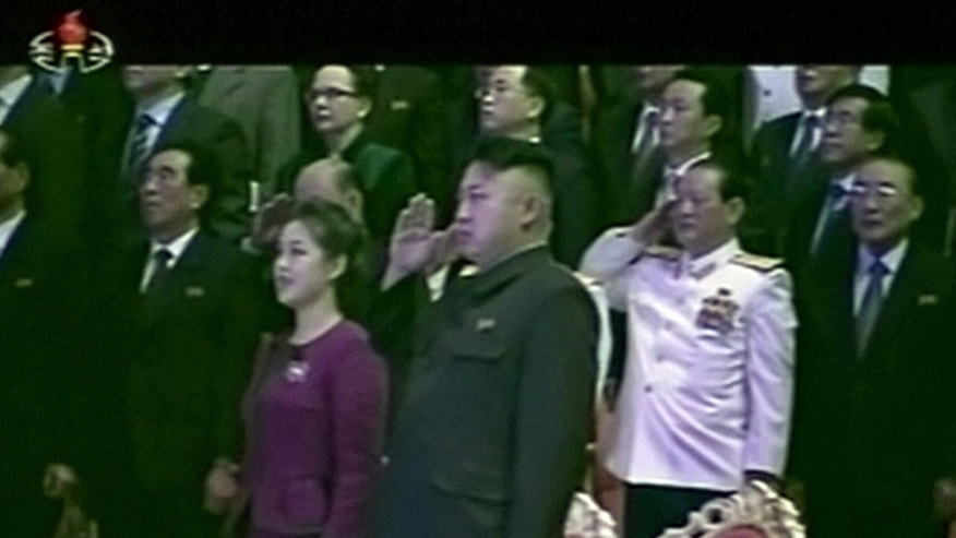 In this Tuesday, Jan. 1, 2013 image made from video, North Korean leader Kim Jong Un, center right, salutes as he and his wife Ri Sol Ju, center left, attend a New Year's concert in Pyongyang, North Korea.