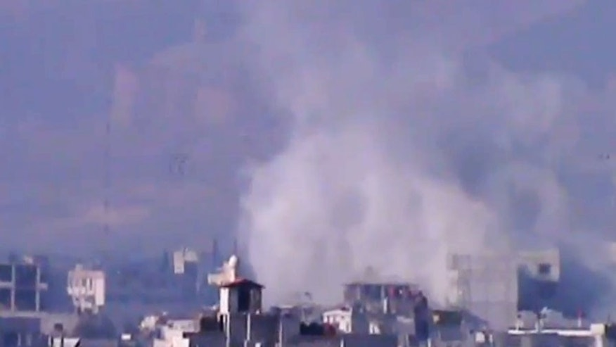 In this image taken from video obtained from the Shaam News Network, which has been authenticated based on its contents and other AP reporting, smoke rises from buildings due to heavy shelling in Damascus countryside, Syria, on Wednesday, Jan. 2, 2013. (AP Photo/Shaam News Network via AP video)