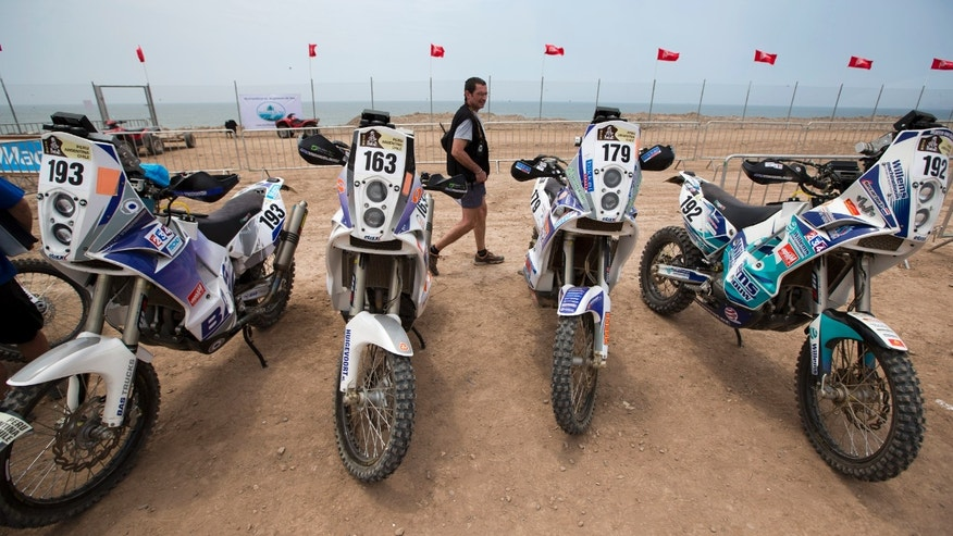 An official inspects motorcycles during the technical and administrative checks of the 2013 edition of the Dakar Rally in Lima, Peru, Thursday, Jan. 3, 2013. The race of over 400 vehicles including cars, bikes, trucks and quads begins on Jan. 5 in Lima, and finishes in Santiago, Chile on Jan. 20. (AP Photo/Victor R. Caivano)