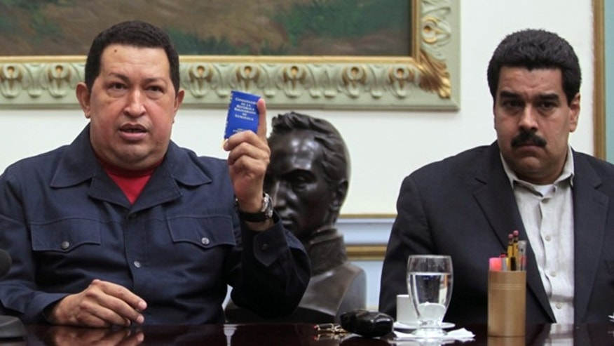 Dec. 8, 2012: Venezuela&#39&#x3b;s President Hugo Chavez, left, holds up a copy of the Venezuelan national constitution as his Vice President Nicolas Maduro looks on during a televised speech at Miraflores presidential palace in Caracas, Venezuela.