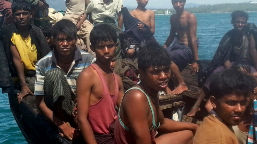 In this photo taken Jan.1, 2013, Rohingya refugees sit in a boat as they are  intercepted by Thai authorities off the sea in Phuket, southern Thailand. Officials said the 73 refugees from Myanmar's Rohingya minority found adrift off a Thai resort island will be repatriated to their homeland. Phuket provincial Governor Maitri Inthusut said Wednesday they declared they were unable to continue their hoped-for journey to Malaysia due to exhaustion and fear of mishaps at sea. (AP Photo)