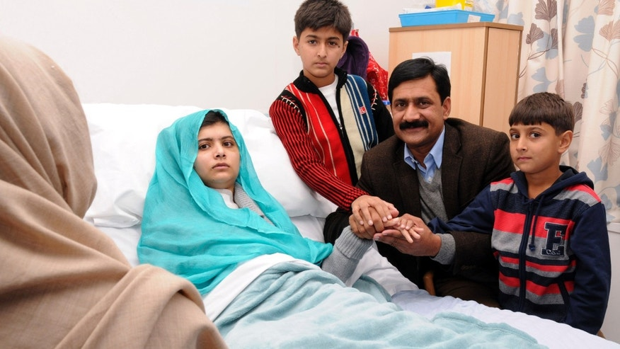 In this undated handout photo issued by Queen Elizabeth Hospital, in Birmingham, England, on Friday, Oct. 26, 2012, Malala Yousufzai in her hospital bed, poses for a photograph, with her father Ziauddin, second right accompanied by her two younger brothers Atal, right and Khushal, centre.