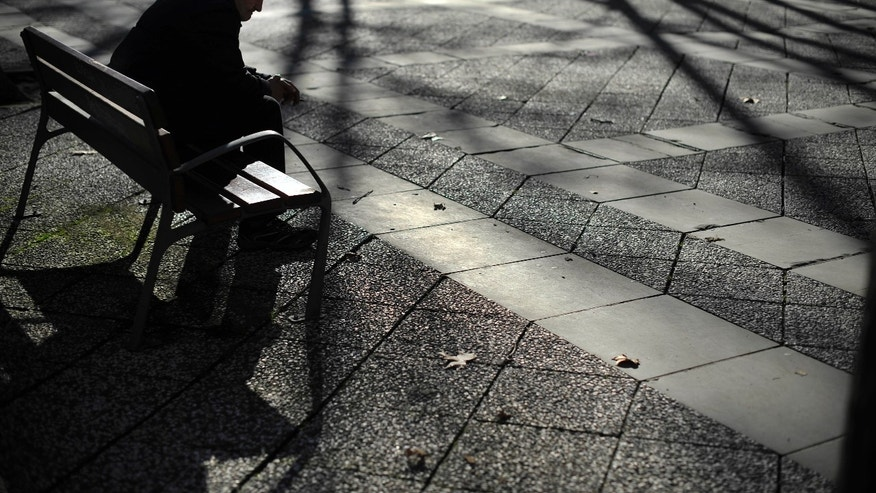 A man rest on a bench as the shadows of trees are seen on the street, in Pamplona northern Spain, on Thursday, Jan. 3, 2013. The number of people registered as unemployed in Spain has gone down, bringing some cheer as the country looks to emerge from recession in 2013. Spain is in the throes of its second recession in just over three years. Its economy has been battered by a collapse in the once-key real estate sector(AP Photo/Alvaro Barrientos)