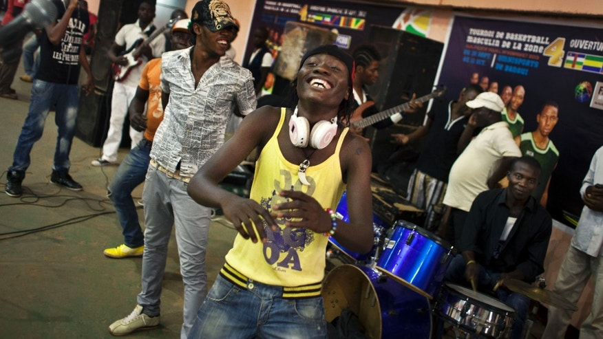 "A youth dances in the rap band entertaining a meeting of the National Youth Council to discuss the current crisis and the message that youth want to send to upcoming peace talks in Libreville, at the basketball stadium in the capital Bangui, Central African Republic Friday, Jan. 4, 2013. The U.N. children's agency UNICEF says it is concerned about a growing number of children being recruited by armed groups in Central African Republic as President Francois Bozize's government faces a rebellion in the north, saying Friday that it has received ""credible reports that rebel groups and pro-government militias are increasingly recruiting and involving children in armed conflict"". (AP Photo/Ben Curtis)"