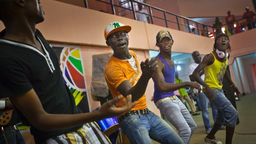"Youths dance in the rap band entertaining a meeting of the National Youth Council to discuss the current crisis and the message that youth want to send to upcoming peace talks in Libreville, at the basketball stadium in the capital Bangui, Central African Republic Friday, Jan. 4, 2013. The U.N. children's agency UNICEF says it is concerned about a growing number of children being recruited by armed groups in Central African Republic as President Francois Bozize's government faces a rebellion in the north, saying Friday that it has received ""credible reports that rebel groups and pro-government militias are increasingly recruiting and involving children in armed conflict"". (AP Photo/Ben Curtis)"