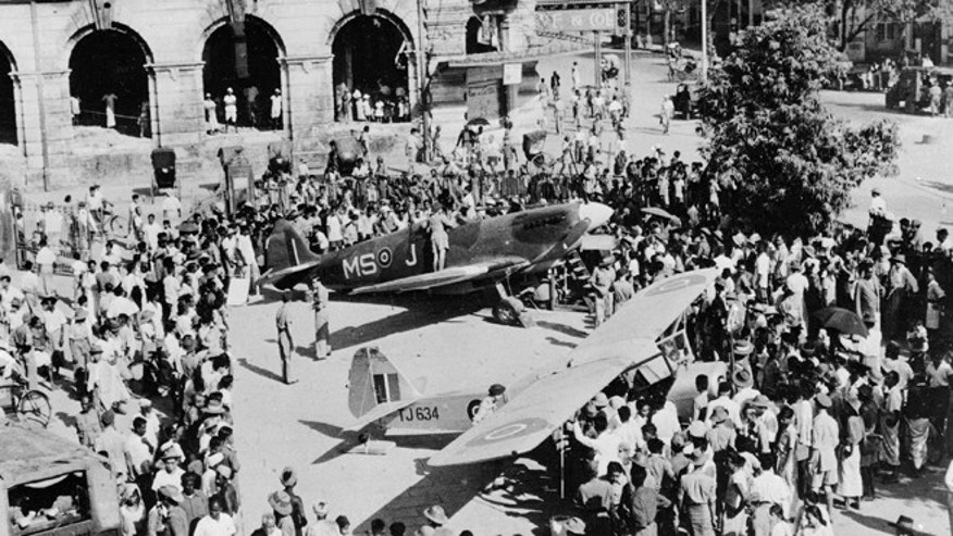 In this April 3, 1946 file photo, the Civic Hall in Rangoon, Burma, is seen with a crowd surrounding a British Spitfire, center, and an Auster aircraft