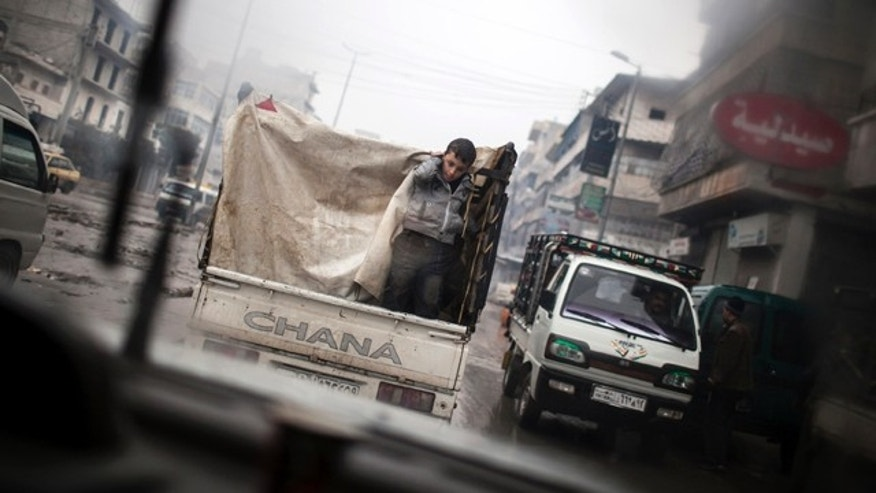 Jan. 5, 2013: A boy is seen through a car window as he rides on the back of a truck in the streets of Aleppo, Syria.
