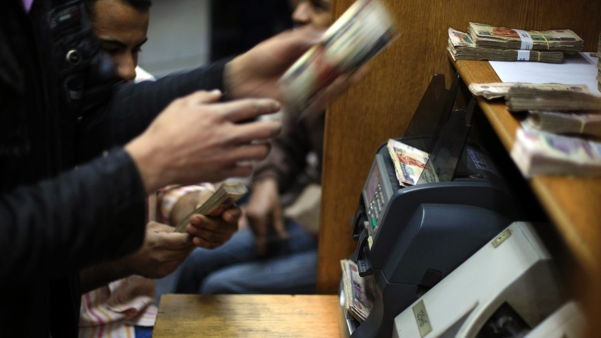FILE - In this Wednesday, Jan. 2, 2013 file photo, Egyptians count money at a currency exchange office in downtown Cairo, Egypt. As Egypt begins the latest round of talks with the International Monetary Fund for a $4.8 billion loan, the government says it will boost international confidence in its economy. However, critics question whether the president's Muslim Brotherhood group has the ability to carry out unpopular austerity measures ahead of crucial parliamentary elections that will take place in the coming months. (AP Photo/Khalil Hamra, File)