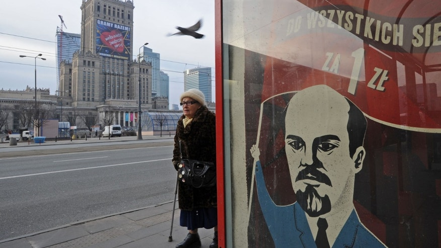 A woman walks past a poster advertising a Polish mobile phone operator with a cartoon of Russian revolution leader Vladimir Lenin, in Warsaw, Poland, Tuesday, Jan. 8, 2013, with the city's landmark, the communist-era Palace of Culture in the background. The operator decided to stop its advertising campaign, as many Poles remember Lenin for shaping a communist regime that killed millions and imposed mass terror in the Soviet Union.  A communist regime was later imposed on Poles against their will by the Soviets after World War II. The writing on the poster reads: 60 minutes to all networks for 1 Polish zloty ( 30 US cents, 25 euro cents). (AP Photo/Alik Keplicz)