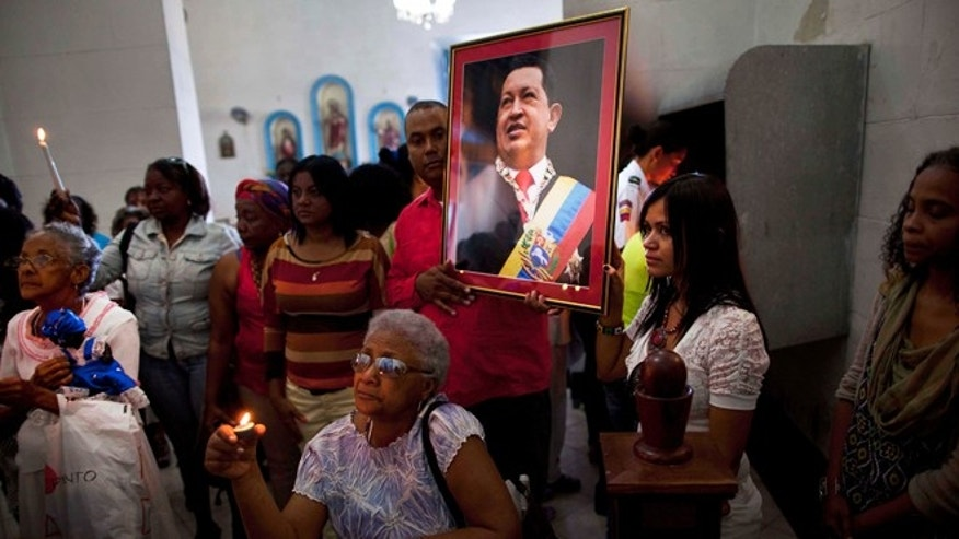 Jan. 8, 2013: Venezuelan embassy workers hold up a framed image of Venezuela's ailing President Hugo Chavez during the monthly Catholic service devoted to the sick at the Church of Our Lady of Regla, in Regla, across the bay from Havana, Cuba.