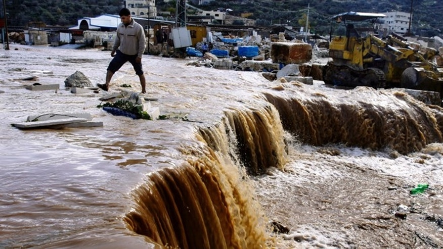 Jan. 9, 2012: Palestinians cross a road flooded and swept away by heavy rains in the northern West Bank village of Kabatyeh.