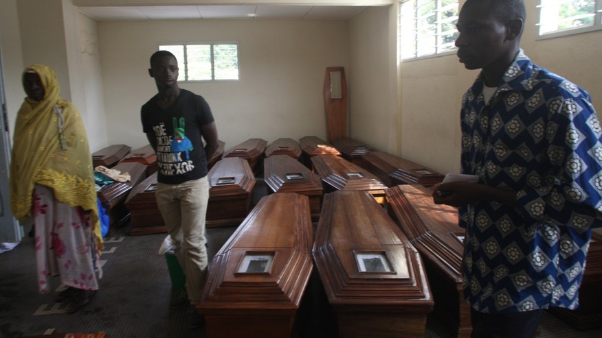 Family members of victims of a New Year's stampede walk amongst coffins at Treichville's University Hospital Center morgue, where relatives were coming to claim the bodies of the 64 killed, in Abidjan, Ivory Coast, Wednesday, Jan. 9, 2013.  Officials said Saturday that the New Year's stampede was caused by a combination of several factors including unofficial tree trunk barricades, the narrowing of a major thoroughfare, bad lighting and a shortage of police officers.(AP Photo/Emanuel Ekra)