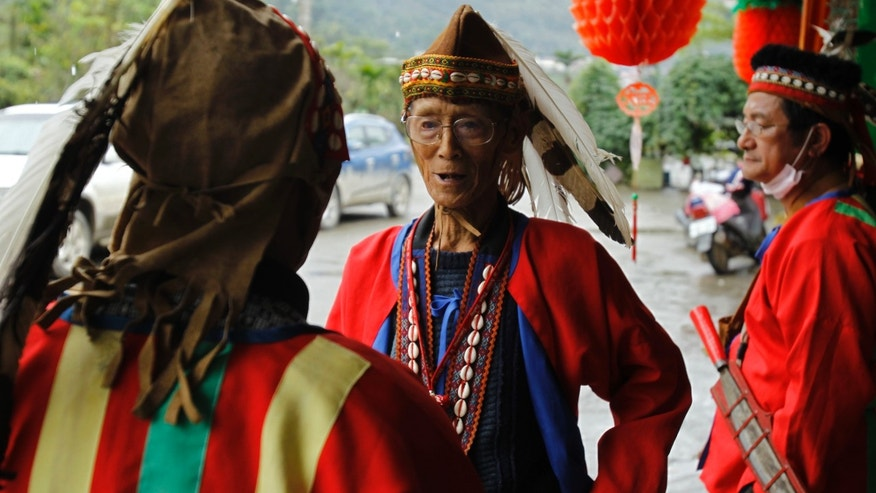 In this photo taken Saturday, Dec. 8, 2012, eighty-year-old aboriginal Mu'u Ka'angena, center, greets his fellow villager, 78-year-old Angai Kamunuana, left, in their aboriginal Kanakanvu mountain village of Dakanua, southern Taiwan. In a race against time, a dedicated Taiwanese linguist is trying to save the historically important aboriginal dialect of Kanakanvu, spoken by only 10 people, from extinction. (AP Photo/Wally Santana)