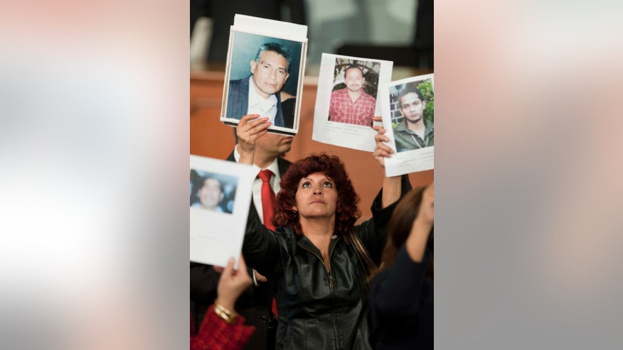 A woman holds up images of alleged crime victims during an event in which Mexico's President Enrique Pena Nieto enacted a general law on victims of crime at Los Pinos presidential residence in Mexico City, Wednesday, Jan. 9, 2013. The law requires local and federal authorities to compensate victims by covering their health and psychiatric care costs and it mandates the creation of a relief fund and a national registry of victims of crime. (AP Photo/Eduardo Verdugo)