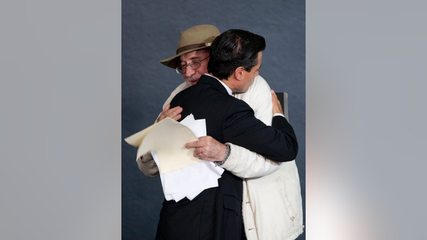 Mexico's President Enrique Pena Nieto, left, and the Mexican poet Javier Sicilia, leader of the Movement for Peace with Justice and Dignity, hug each other during an event to enact a general law on victims of crime at Los Pinos presidential residence in Mexico City, Wednesday, Jan. 9, 2013. The law requires local and federal authorities to compensate victims by covering their health and psychiatric care costs and it mandates the creation of a relief fund and a national registry of victims of crime. (AP Photo/Eduardo Verdugo)