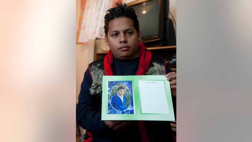 Enrique Martinez shows a photograph of his brother Samuel, who according to authorities was killed by feral dogs on Saturday, during an interview at his home in Iztapalapa, Mexico City. Tuesday, Jan. 8, 2013. The fatal mauling of four people by feral dogs in a Mexico City park set off debate Tuesday about the city's love/hate relationship with its dog population, and the guilt or innocence of 25 animals trapped near the scene of the nightmarish killings. (AP Photo/Eduardo Verdugo)