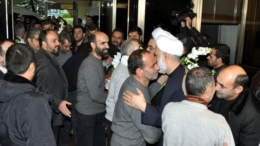 In this photo released by the Syrian official news agency SANA, freed Iranian hostages who were captured by the Syrian rebels, left, received by Iranian officials, left, upon their arrival at a hotel, in Damascus, Syria, Wednesday Jan. 9, 2013. Rebels freed 48 Iranians on Wednesday in exchange for more than 2,000 prisoners, including women and children, held by Syrian authorities — a deal struck after rare negotiations involving regional powers Turkey, Qatar and Iran. (AP Photo/SANA)