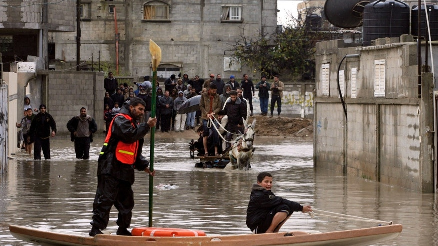 A Palestinian rescue worker helps a boy cross a flooded street in Rafah southern Gaza Strip, Wednesday, Jan. 9, 2013. In Gaza, civil defense spokesman Mohammed al-Haj Yousef said storms have cut electricity powering thousands of homes and rescuers were sent to evacuate dozens of people. (AP Photo/Eyad Baba)