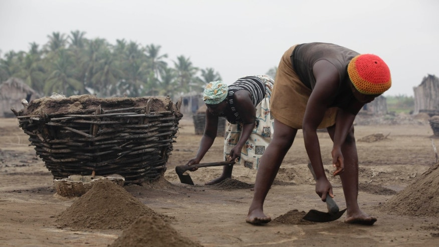 Kakpo Augustine, left, and Victorine Accrombessi, right, dig up soil in the village of Djegbadji near Ouidah, Benin, on Friday, Jan. 11, 2013. Artisanal salt farmers in this village in Benin dig off the top layer of soil near their hut homes, then filter water through the dirt to draw out salt. They later boil the water to collect the salt and sell it. On average, they sell enough for two salt shakers for about $1. (AP Photo/Sunday Alamba)