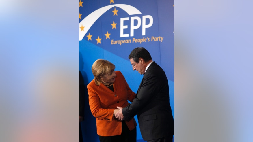 German Chancellor Angela Merkel shakes hands with Cyprus' main opposition Democratic Rally party leader Nicos Anastasiades, right, following a European People's Party (EEP) meeting in Cyprus' southern coastal resort of Limassol in an extraordinary summit on Friday, Jan. 11, 2013. Among the topics of discussion at the meeting hosted by the leader of Cyprus' main opposition Democratic Rally party Nicos Anastasiades will be the EU budget. Anastasiades is currently leading opinion polls as the top contender ahead of the country's Feb. 17 presidential election.  (AP Photo/Petros Karadjias)
