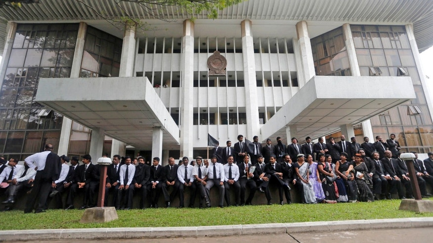 Sri Lankan lawyers sit in protest against the government's impeachment bid to remove chief justice Shirani Bandaranayake at the court complex building in Colombo, Sri Lanka, Friday, Jan. 11, 2013. The lawyers accuse the government of violating the constitution by continuing the impeachment process against Bandaranayake despite court orders against it. They say the impeachment plan is a part of a government move to undermine the independence of the judiciary. (AP Photo/Eranga Jayawardena)