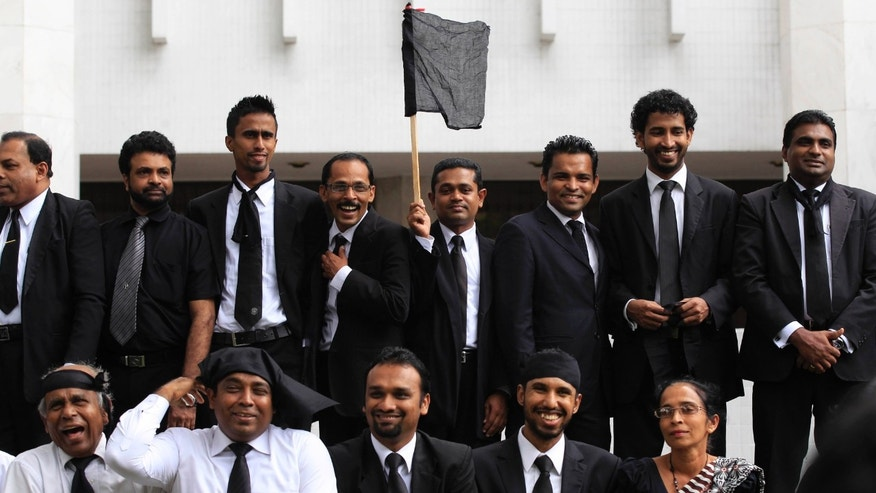 A Sri Lankan lawyer holds a black flag as others pose for the media in protest against the government's impeachment bid to remove chief justice Shirani Bandaranayake at the court complex building in Colombo, Sri Lanka, Friday, Jan. 11, 2013. The lawyers accuse the government of violating the constitution by continuing the impeachment process against Bandaranayake despite court orders against it. They say the impeachment plan is a part of a government move to undermine the independence of the judiciary. (AP Photo/Eranga Jayawardena)