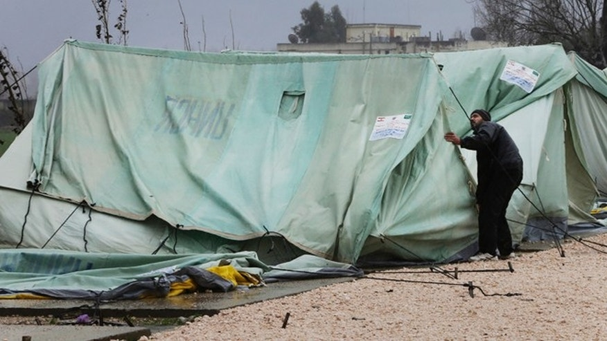 Jan. 7, 2013: A Syrian refugee man, fixes a tent that was blown off by the wind, at a temporary refugee camp in the eastern Lebanese town of Marj near the border with Syria, Lebanon.