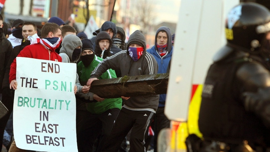 Loyalist protesters attack police lines, at the Albertbridge Road, near the nationalist Short Strand area of Belfast, Northern Ireland, Saturday Jan. 12, 2013. Police used water cannons as four officers were injured during sectarian clashes between loyalists and republicans in east Belfast, Saturday. Trouble flared after a city centre demonstration against the council's decision to limit the number of days the Union flag is flown from City Hall (AP Photo/Paul Faith/PA) UNITED KINGDOM OUT
