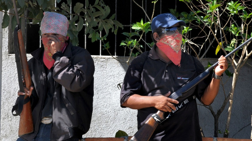 People wearing bandanas and carrying small arms man a checkpoint in Teconoapa, in the Mexican state of Guerrero, Friday, Jan. 11, 2013. Several hundred civilians have taken up arms in two towns in the southwestern Mexico state and are arresting people suspected of crimes and imposing a curfew. Leaders said they were acting against crime and insecurity. Guerrero Gov. Angel Aguirre Rivero responded Friday by announcing that security in the region would be bolstered by sending in Mexican soldiers and marines and federal and state police officers. (AP Photo/Bernandino Hernandez)