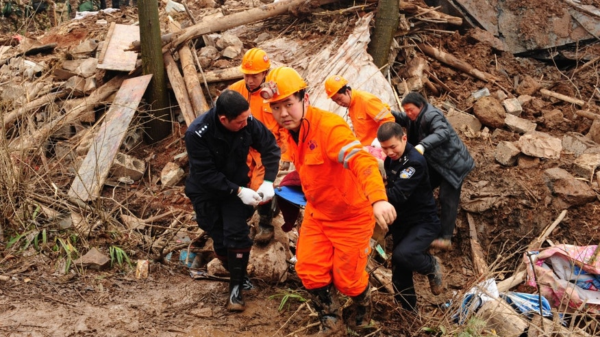 In this Jan. 11, 2013 photo provided by China's Xinhua News Agency, rescuers remove a body from the mud-inundated debris after a landslide hit Zhaojiagou in Zhenxiong County,  southwest China's Yunnan Province. A landslide swept through a village in the steep, snow-dusted mountains of southern China on Friday, killing at least 32 people, the local government said. (AP Photo/Xinhua, Shi Shengming) NO SALES