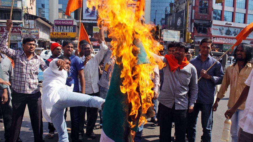 Activists of hindu nationalist Vishwa Hindu Parishad (or World Hindu Council) burn a flag of Pakistan during a protest in Hyderabad, India, Friday, Jan. 11, 2013. India has formally complained about an attack on an Indian army patrol in the disputed Himalayan region of Kashmir that killed two soldiers and left their bodies mutilated. India says Pakistani troops crossed the cease-fire line Tuesday and attacked Indian soldiers patrolling in the Mendhar region before retreating. (AP Photo/Mahesh Kumar  A.)