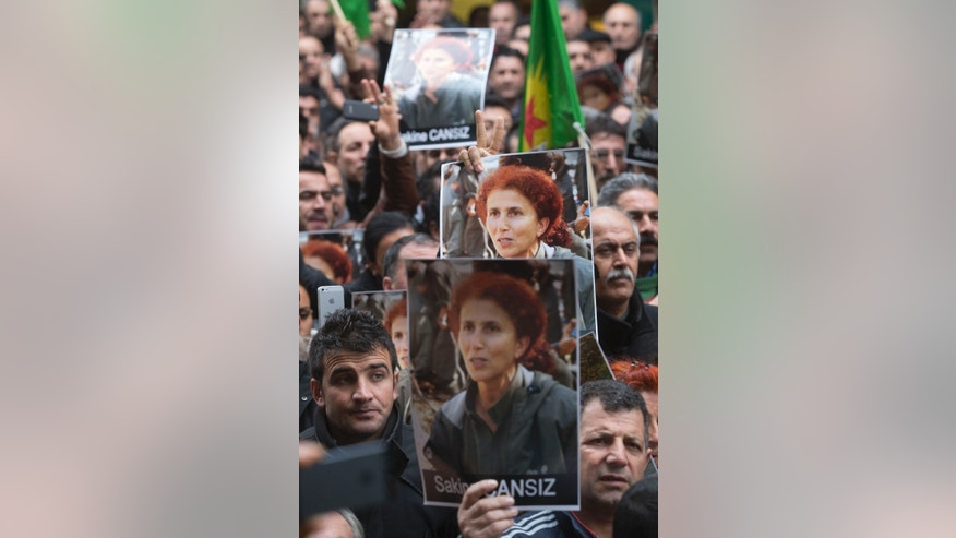 Kurds gathering outside the Kurdish culture center in Paris, holding pictures of the killed kurdish activists found killed Thursday in the French capital, Friday, Jan. 11, 2013. Turkey's prime minister suggested Friday that a feud among Kurdish rebels was behind the shooting deaths of three Kurdish activists in Paris, and the rebels said it was an attempt to undermine peace talks that their jailed leader is holding with Turkey. (AP Photo/Michel Euler)