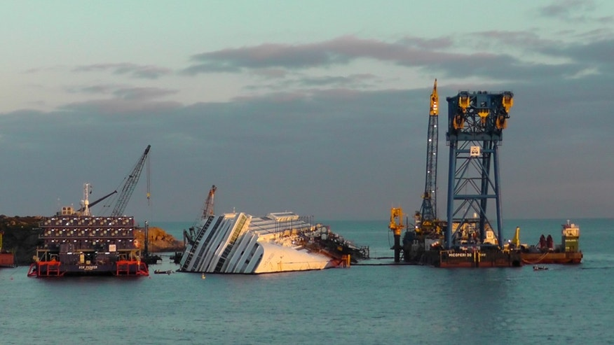 The cruise ship Costa Concordia, leaning on its side, is seen just off the coast of the Tuscan island of Giglio, Italy, Saturday, Jan. 12, 2013. As if the nightmares, flashbacks and anxiety weren't enough, passengers who survived the terrifying grounding and capsizing of the Costa Concordia off Tuscany have come in for a rude shock as they mark the first anniversary of the disaster on Sunday. Ship owner Costa Crociere SpA, the Italian unit of Miami-based Carnival Corp., sent several passengers a letter telling them they weren't welcome at the official anniversary ceremonies on the island of Giglio where the hulking ship still rests. Costa says the day is focused on the families of the 32 people who died Jan. 13, 2012, not the 4,200 passengers and crew who survived. (AP Photo/Paolo Santalucia)