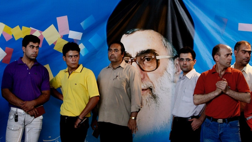FILE - In this Friday, June 12, 2009 file photo, Iranian men line up as they wait to vote for presidential election, while they stand in front of a picture of the supreme leader Ayatollah Ali Khamenei, at a polling station, in downtown in Tehran, Iran. Elections to pick Iran's next president are still five months away, but that's not too early for some warning shots by the country's leadership. The message to anyone questioning the openness of the June vote: Keep quiet. (AP Photo/Vahid Salemi, File)