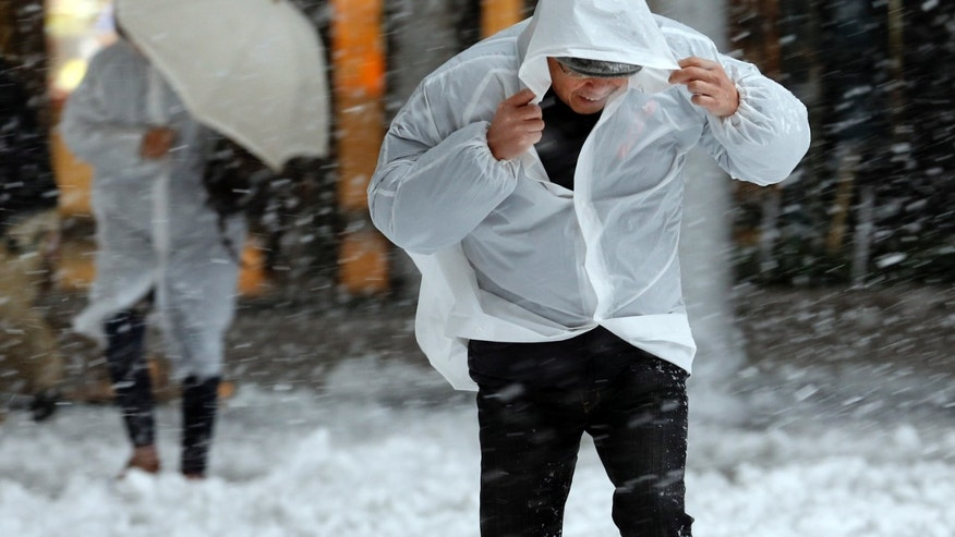 People attempt to shield themselves as it snows in Tokyo, Monday, Jan. 14, 2013. (AP Photo/Koji Sasahara)