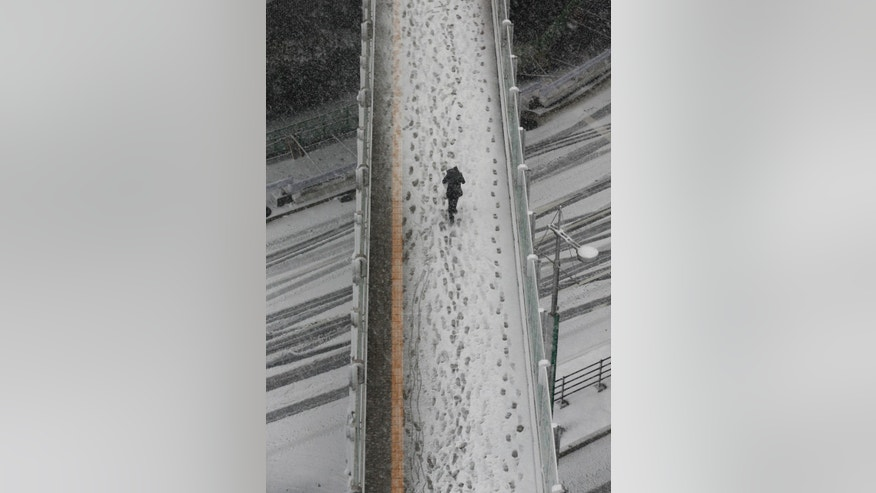 A man walks on a pedestrian bridge in the snow in Tokyo Monday, Jan. 14, 2013. This winter's first snow in Tokyo severely disrupted train services in the Japanese capital. (AP Photo/Koji Sasahara)